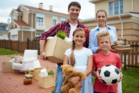 boy lady: Happy family looking at camera on background of their new house