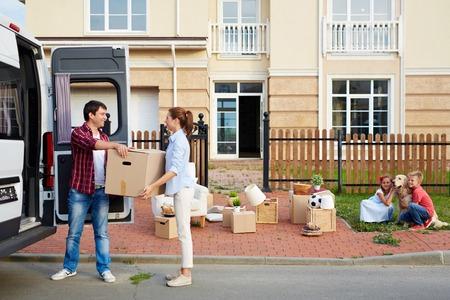 Jonge man geeft zijn vrouw doos tijdens het lossen dingen uit van