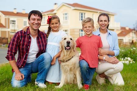 Familieleden en hun hond zittend op het gras van nieuw huis