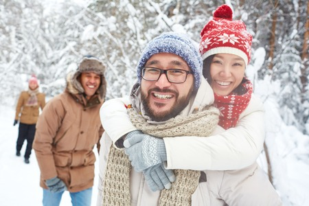 winter park: Affectionate couple and their friends having fun in winter park Stock Photo