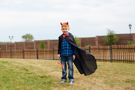 Little boy in costume of devil standing on grass in natural environment