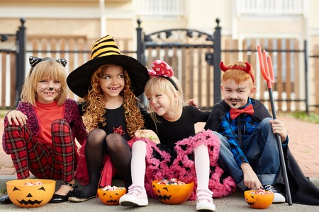 repent: Four little friends in Halloween costumes eating their treats Stock Photo