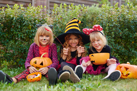 Friendly kids with symbols of Halloween sitting on grass