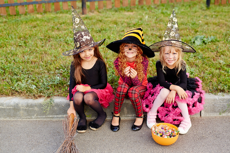Row of Halloween girls in witch hats sitting by road Stock Photo