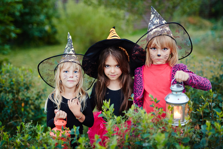 Spooky girls dressed as witches looking at camera