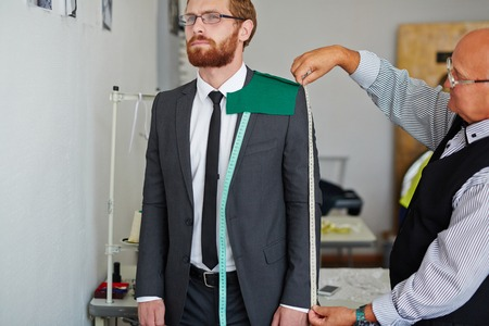 sleeve: Tailor measuring length of jacket sleeve worn by man Stock Photo