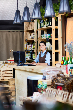 stocktaking: Small business owner standing by cashdesk
