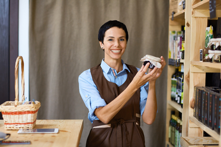 stocktaking: Happy assistant with jar of honey looking at camera in her own shop