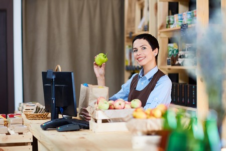 stocktaking: Smiling cashier with green pepper working in supermarket