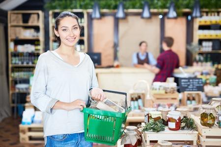 Cliente felice con il cestino della spesa che esamina macchina fotografica nel supermercato