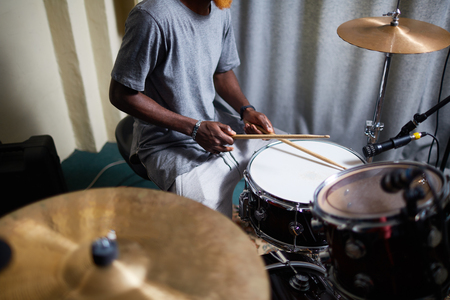 Young man with drumsticks recording his music in home studio