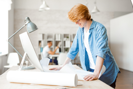 bocetos de personas: Young engineer looking at sketch at workplace Foto de archivo