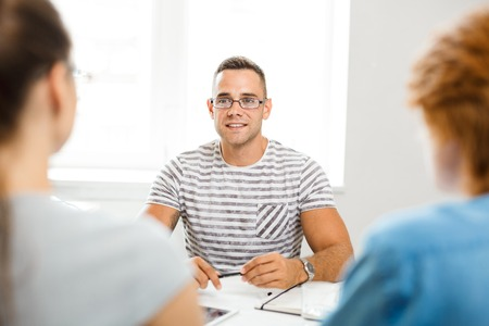 Confident employer talking to young specialists during interview