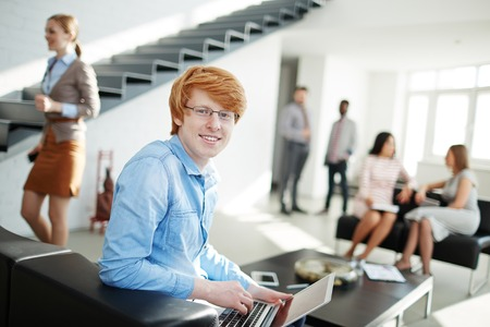 office environment: Happy young man looking at camera in working environment in office