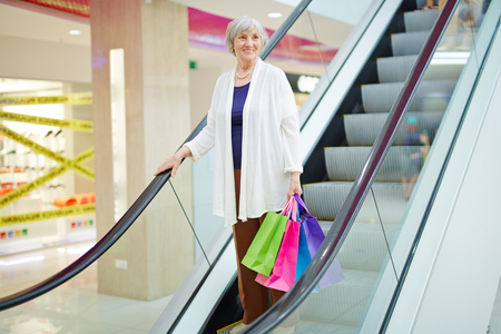 paperbags: Smiling senior woman with paperbags descending on escalator Stock Photo