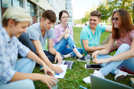revising: Circle of students revising home assignment on campus lawn Stock Photo