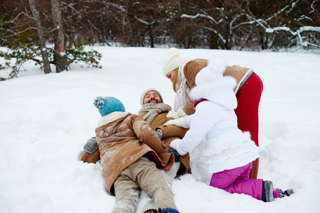 Playful family having fun in snowdrift