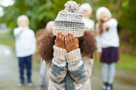 Crying girl hiding her face while classmates mocking at her