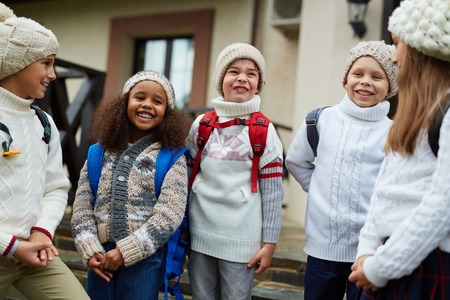 schoolkids: Group of happy schoolkids in knitted caps and sweaters