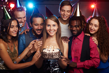 clubber: Happy girl with birthday cake looking at camera among her friends Stock Photo
