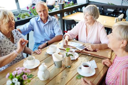 노인들은 차와 대화를 위해 테이블에 모였습니다. 스톡 콘텐츠