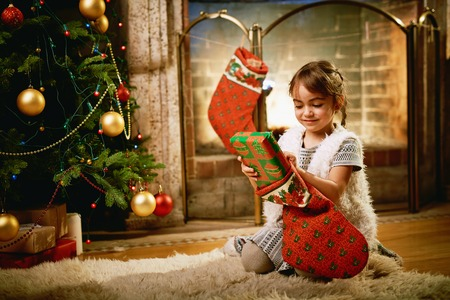 Little girl putting xmas surprise into gift sock