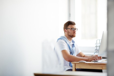 remote: Serious young businessman networking in front of computer