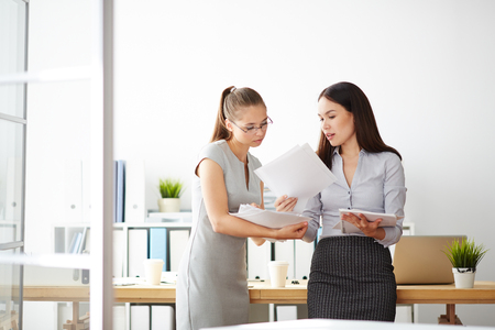 Two young accountants discussing papers during working day