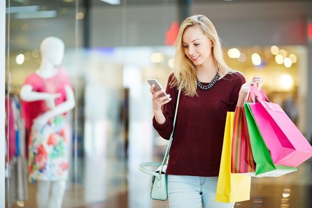paperbags: Girl with smartphone and paperbags after shopping