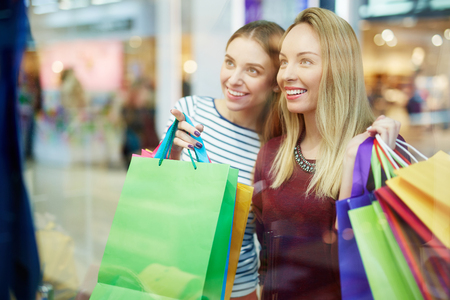 shopper: Happy shopper pointing at something in shop-window Stock Photo