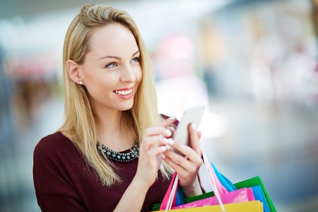 woman bag: Pretty young customer with cellphone spending leisure in shopping center Stock Photo