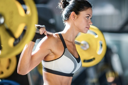 Sportive female with weight working out in gym