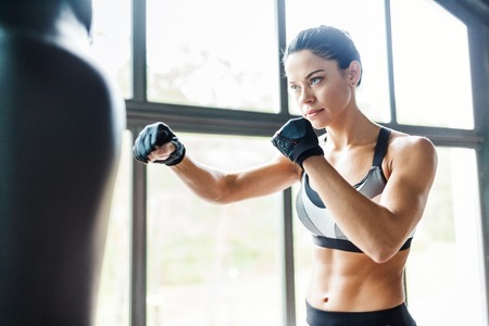 female fighter: Female fighter practicing kickboxing exercise in gym Stock Photo