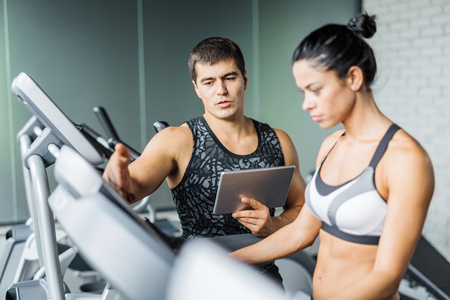 regulate: Young trainer explaining how to regulate speed of treadmill to active girl