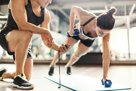 Trainer with stopwatch and young woman exercising with dumbbells