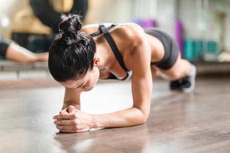 Female athlete doing planks on the floor