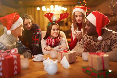 Amici interculturali che hanno teaaa alla festa di Natale a casa Archivio Fotografico - 63745798