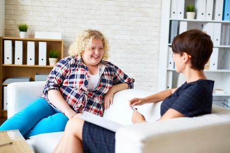 Junge Frau mit Übergewicht im Gespräch mit ihrem Psychologen Standard-Bild - 63745805