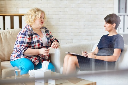 attentively: Serious psychologist listening attentively to her patient Stock Photo