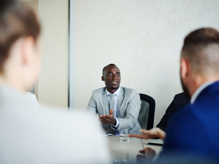 proficient: Business expert consulting young colleagues at briefing