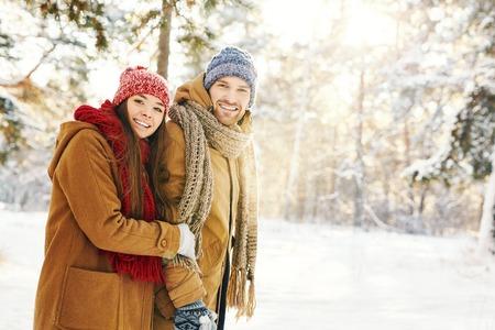 Happy couple in winterwear taking walk in forest
