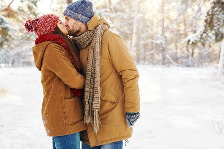 winter couple: Amorous young couple in winterwear kissing outdoors Stock Photo