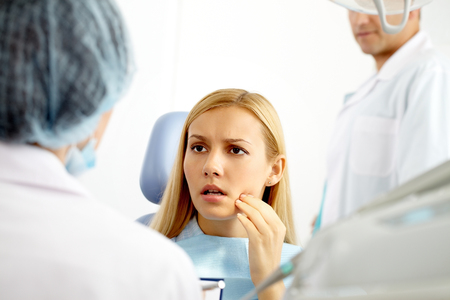A young woman at dentist office talking to the doctor Stock Photo