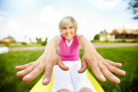 Stretched image of a woman doing exercises with focus on her hands Stock Photo