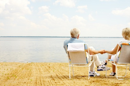 long life: Rear view of senior couple resting in chaise lounges on lakeside and holding hands