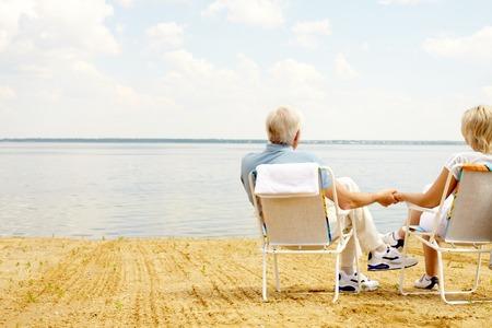 Vista trasera de una pareja mayor que se reclina en camastros en la orilla del lago y de la mano Foto de archivo - 63745954