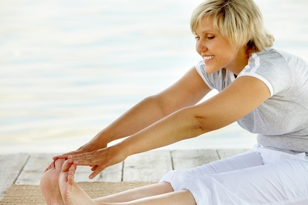 mature woman sitting: Mature woman sitting on floor and stretching