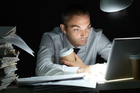 coffee hour: Businessman sitting at his desk and working till night