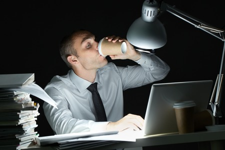 coffee hour: Businessman drinking coffee at desk at night
