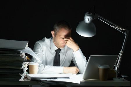 Üzletember ül íróasztal teljes papírokkal túlterheljék munka